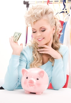 Portrait de belle femme avec tirelire et argent