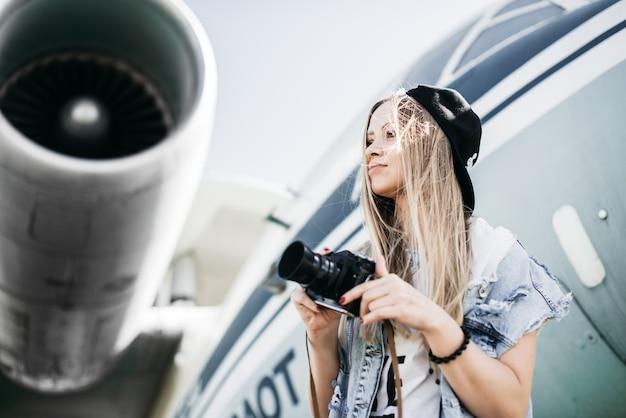 Portrait d'une belle femme touristique avec une vieille caméra vintage de film posant près de l'avion