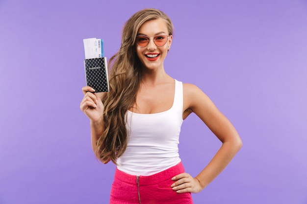 Portrait de la belle femme en vêtements d'été et lunettes de soleil souriant et tenant des billets de passeport et de vacances