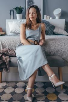 Portrait d'une belle femme vêtue d'une robe à la maison dans la chambre