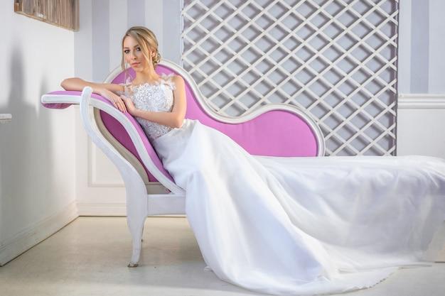 Portrait d'une belle femme vêtue d'une robe de mariée blanche avec un beau maquillage et des cheveux sur le canapé