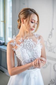 Portrait d'une belle femme vêtue d'une robe de mariée blanche avec un beau maquillage et une coiffure