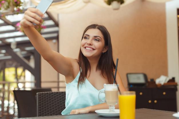 Portrait de belle fille à l'aide de son téléphone portable au café