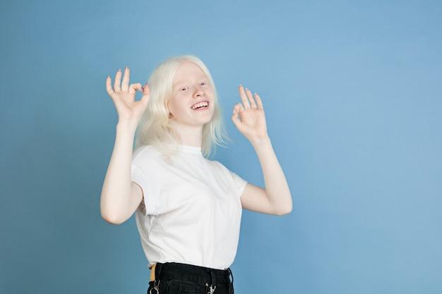 Portrait de belle fille albinos caucasienne isolée sur mur bleu