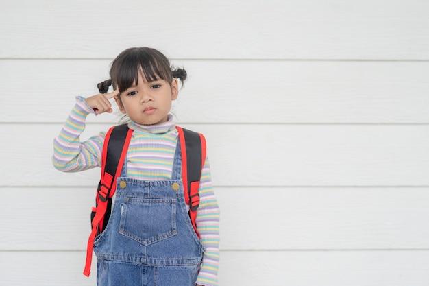 Portrait de belle fille asiatique pensant sur fond blanc