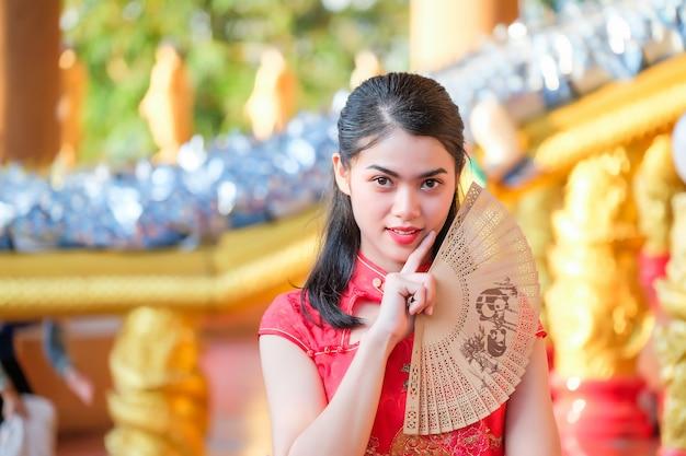 Portrait belle fille asiatique portant une robe rouge cheongsam tenir un ventilateur