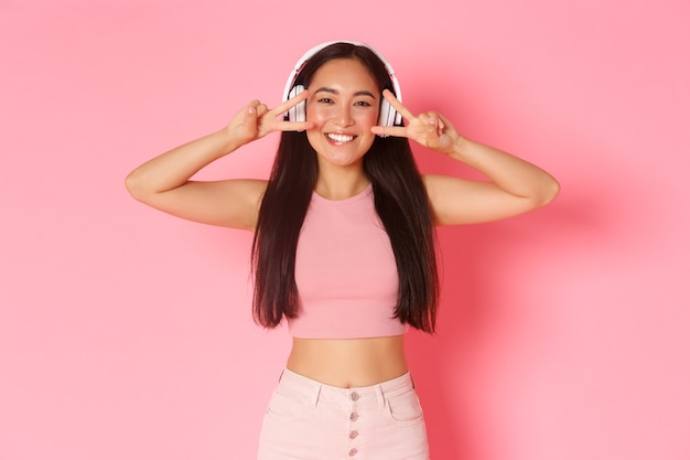 Portrait de belle fille asiatique souriante dans des écouteurs sans fil, écouter de la musique, profiter de la qualité sonore, montrer la paix ou des gestes kawaii voer les yeux et sourire heureux sur le mur rose.
