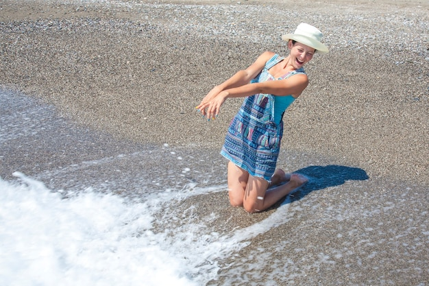 Portrait d'une belle fille au chapeau souriant joyeusement et posant dans les vagues sur la plage.