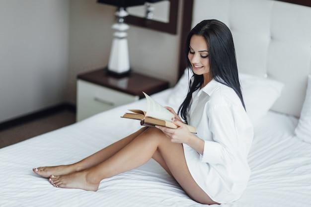 Portrait de la belle fille au lit avec livre