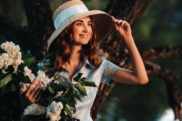 Portrait d'une belle fille aux cheveux longs, un chapeau de paille et une longue robe d'été avec des fleurs lilas dans le jardin.