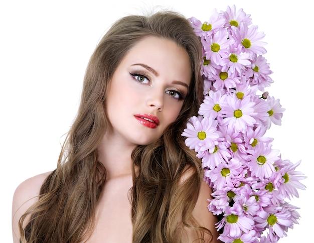 Portrait de belle fille avec de beaux cheveux longs et fleurs de printemps - espace blanc