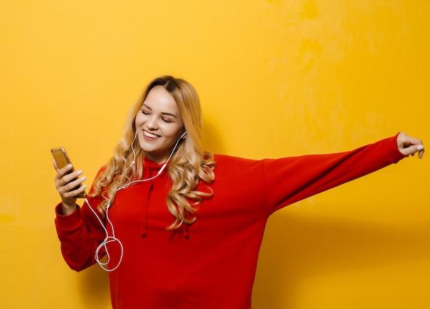 Portrait d'une belle fille blonde heureuse, écouter de la musique dans les écouteurs et danser sur le mur jaune