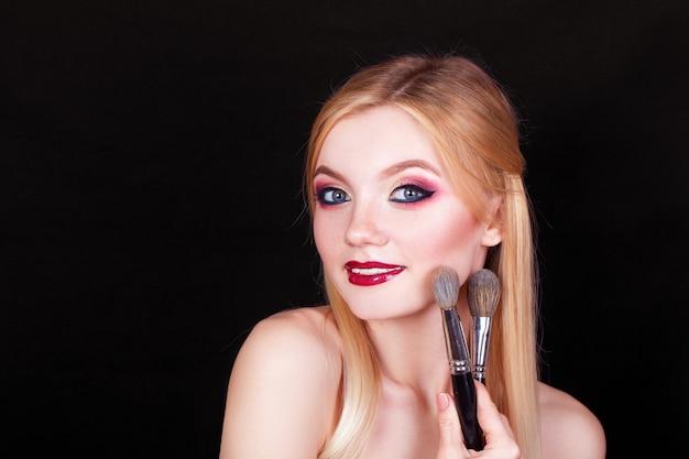 Portrait d'une belle fille blonde avec des pinceaux pour le maquillage dans les mains sur fond noir