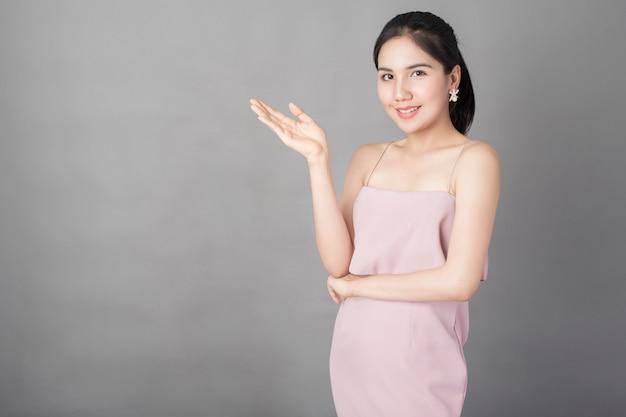 Portrait de belle fille en bonne santé en robe rose sur fond gris, studio tourné