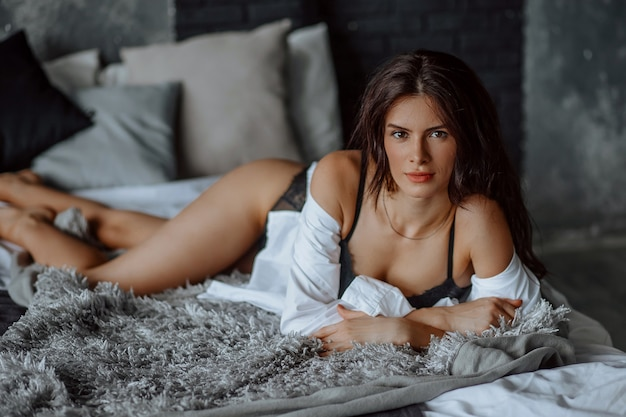 Portrait de belle fille brune allongée sur le lit en lingerie