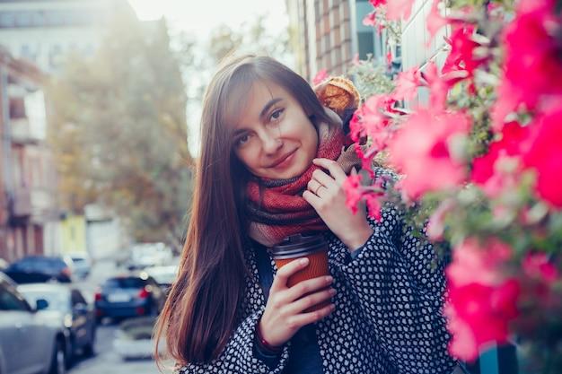 Portrait de belle fille brune avec boisson à emporter dans la rue. écharpe et manteau d'automne dans la ville. vue imprenable sur une femme d'affaires avec une tasse de café marchant dans la rue de la ville.