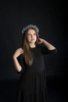 Portrait de la belle fille brune en guirlande de fleurs séchées sur fond noir, concept émotionnel