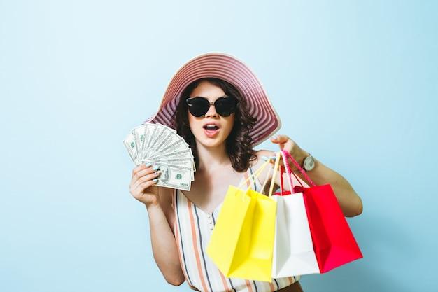 Portrait d'une belle fille brune heureuse isolée sur fond bleu tenant des billets en argent et un sac à provisions