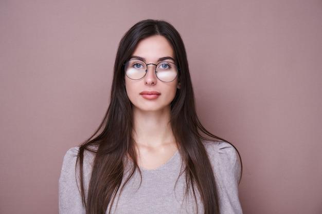 Portrait de la belle fille brune avec des lunettes et une expression faciale grave isolée dans un mur marron