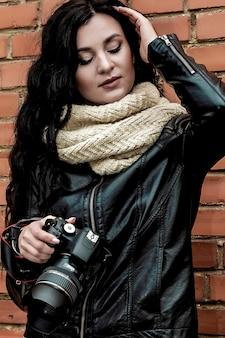 Portrait d'une belle fille brune photographe aux longs cheveux bouclés dans des vêtements chauds d'automne