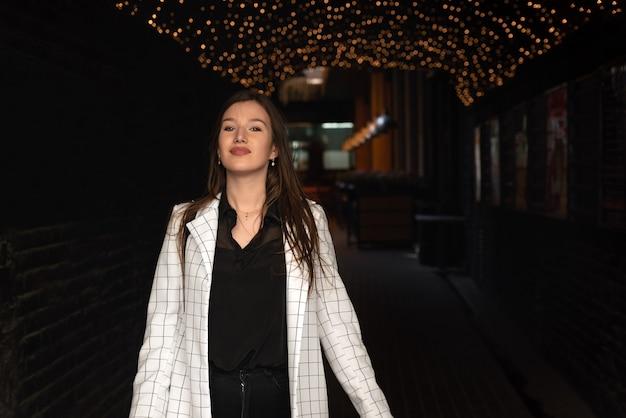 Portrait de la belle fille brune sur la rue du soir, fond de guirlandes.