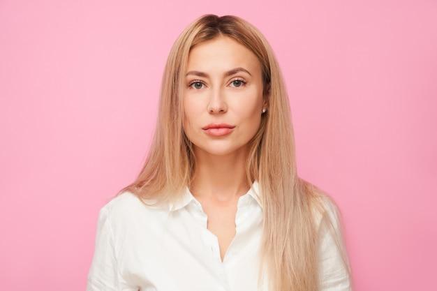 Portrait de belle fille de bureau blonde en chemise blanche en regardant la caméra isolée sur fond de studio rose