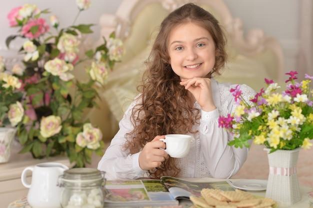 Portrait d'une belle fille buvant du thé à la maison