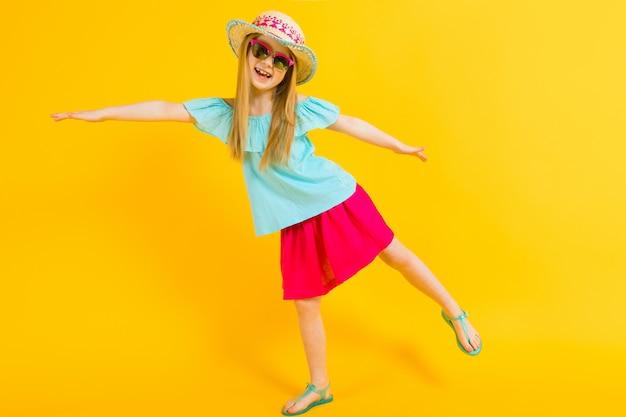 Portrait d'une belle fille avec un chapeau, des lunettes de soleil, une robe d'été et des sandales.