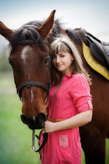 Portrait de la belle fille avec un cheval brun dans le parc