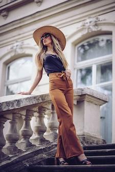 Portrait de belle fille cool gesticulant en chapeau et des lunettes de soleil sur le mur de grunge