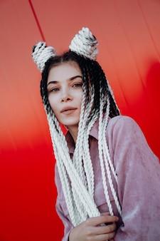 Portrait de belle fille cool avec des nattes sénégalaises et des dreadlocks sur mur rouge