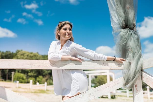 Portrait de belle fille dans le belvédère en bois blanc sur le lac, profiter et se détendre dans la nature