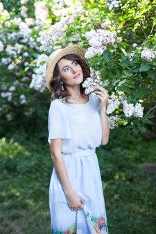 Portrait d'une belle fille dans un chapeau de paille dans un jardin lilas
