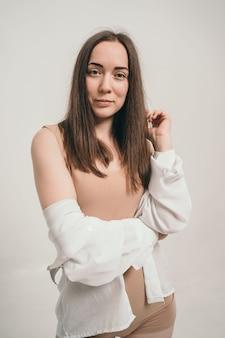 Portrait d'une belle fille dans une chemise blanche jolie brune regarde dans le cadre un g courageux et doux ...