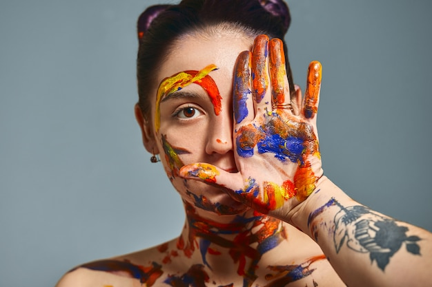 Portrait d'une belle fille dans la peinture. closeup portrait of a girl with face and hands with different paint. concept d'art de mode, beauté, personnes créatives personnes indépendantes