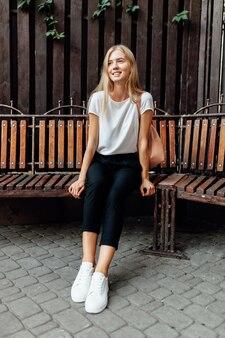 Portrait d'une belle fille dans un t-shirt blanc assis sur un banc contre un mur à feuilles caduques en bois