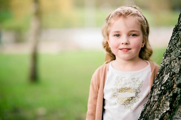 Portrait de belle fille debout près d'un arbre