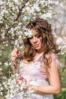 Portrait d'une belle fille enceinte dans le jardin de printemps