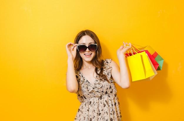 Portrait d'une belle fille excitée avec lunettes de soleil tenant des sacs shopping isolés sur jaune