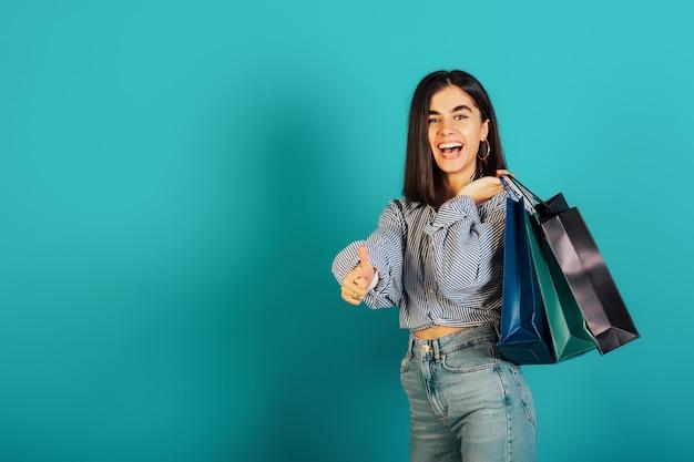 Portrait d'une belle fille excitée portant une chemise bleue et un jean détient des sacs à provisions isolés sur fond bleu