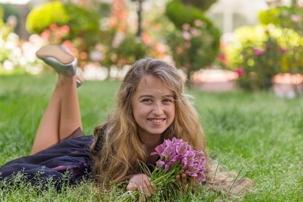 Portrait de belle fille à l'extérieur couché, souriant tout en tenant des fleurs en t-shirt noir pendant la journée.