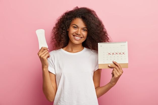 Portrait de belle fille féminine a une coiffure afro, tient un calendrier mensuel, une serviette hygiénique propre