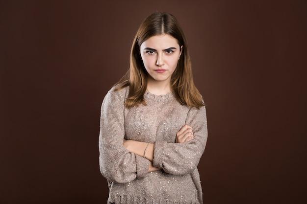 Portrait de belle fille fronçant les sourcils de mécontentement, portant un pull ample à manches longues, les bras croisés. jolie jeune femme en posture fermée.