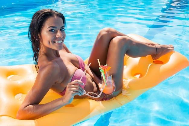 Portrait d'une belle fille heureuse allongée sur un matelas pneumatique dans la piscine