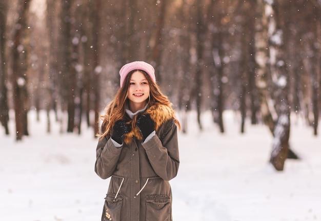 Portrait d'une belle fille heureuse en hiver dans le parc par une journée ensoleillée