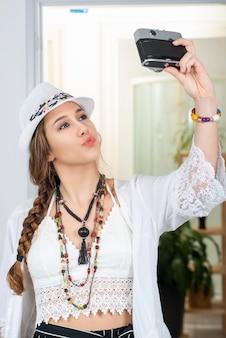 Portrait de belle fille hippie faisant un selfie avec appareil photo antique