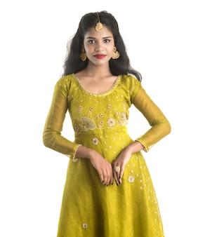 Portrait de la belle fille indienne traditionnelle posant sur le mur blanc