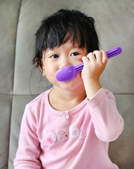 Portrait de belle fille jouant avec une cuillère en mangeant
