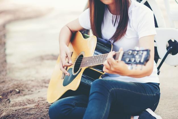 Portrait de belle fille jouant de la guitare avec vélo à la nature
