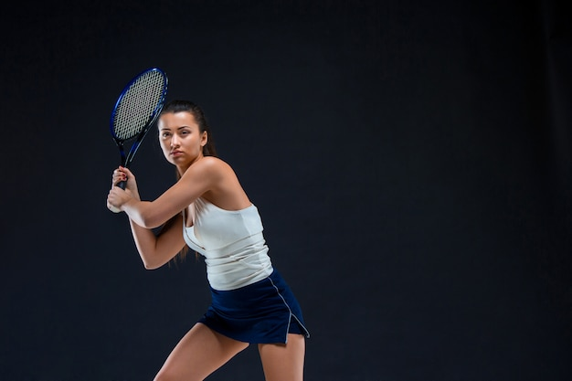 Portrait de la belle fille joueur de tennis avec une raquette sur mur sombre